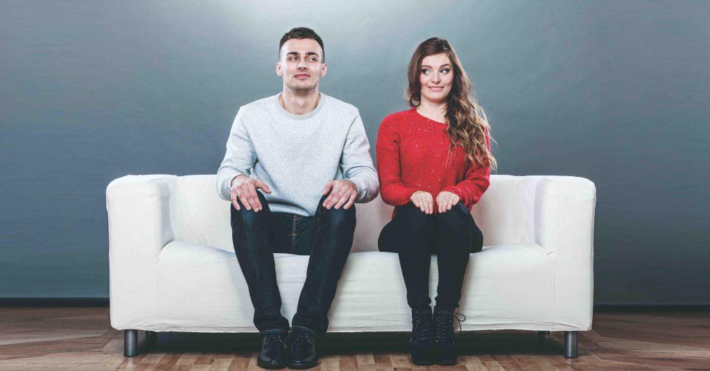 shy-woman-man-sitting-on-sofa-first-date